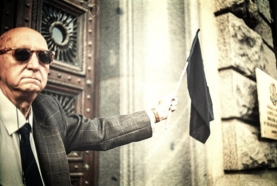 An elderly gentleman holding the black flag of anarchy and raising it high. The photo is taken wi...