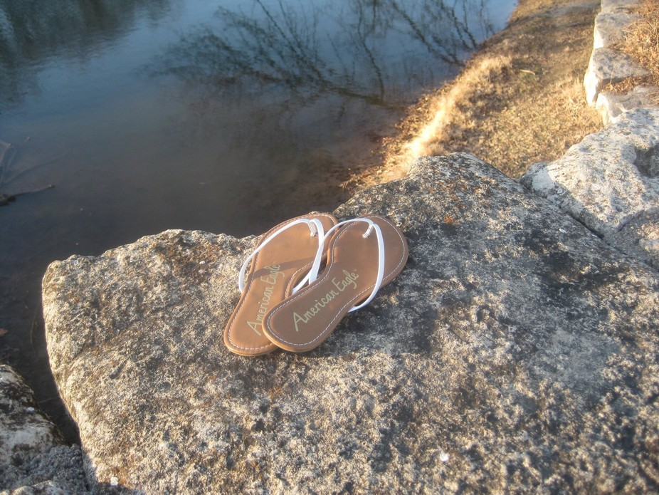 White flip flop sandals on rocks near a pond.