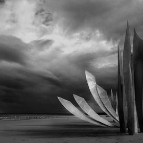 LES BRAVES, the sculpture by Anilore Banon, on Omaha Beach, under a threatening sky, a monument, to the Americans who liberated France.  It was p...