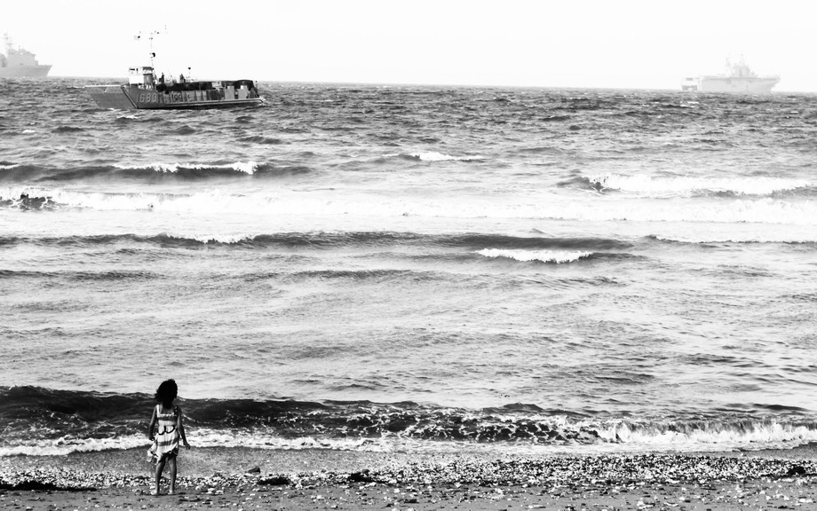 Local girl looks out to the horizon at the ships coming in from a long fishing trip amongst the r...