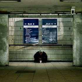 A homeless man at the end of the walkway at London underground.