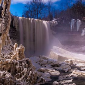 The trees and plants are frozen from the spray of the waterfall making it seem almost like a moon landscape.