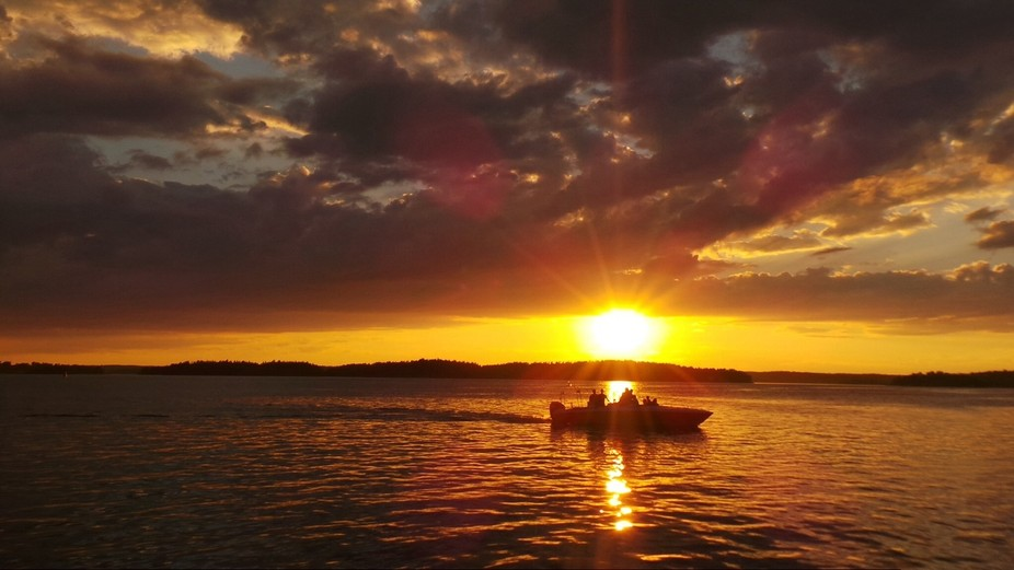 Boat passes through suns rays on the water in Stockholm archipelago