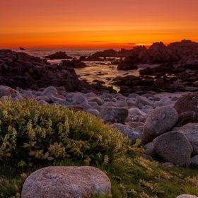 Sunset near Monterey, California with rocks in the foreground.