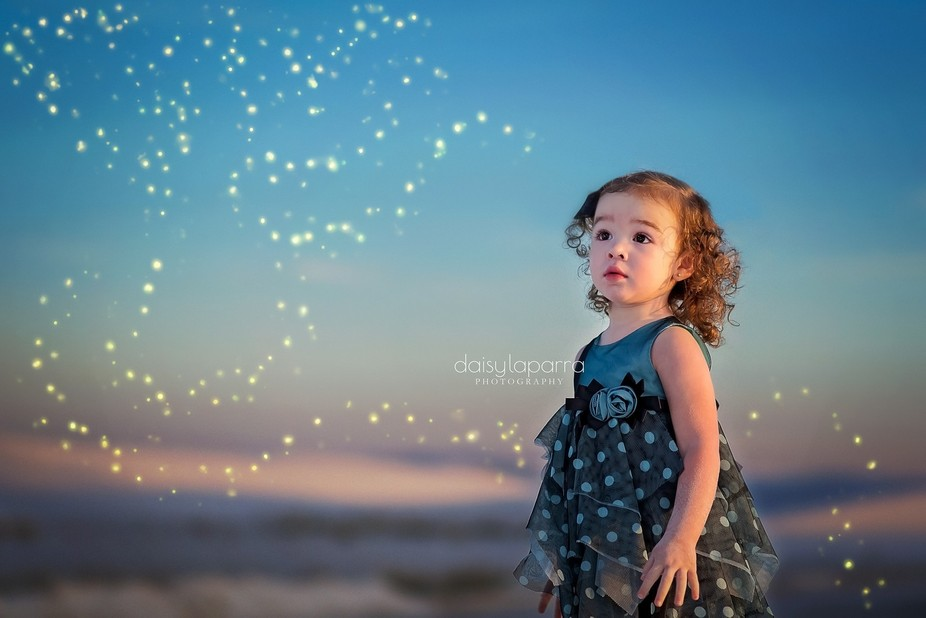 Gorgeous little girl with curly light brown hair in awe of fireflies
