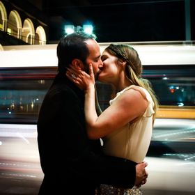 A couple stops for a kiss on a busy city street.