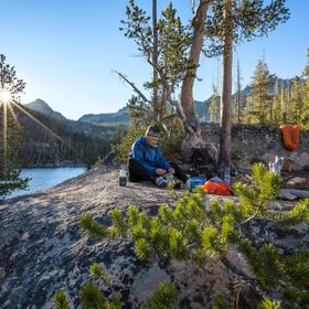A backpacker enjoys a hot breakfast as the first rays of the morning sun touch down over Shangri-La in Idaho's Sawtooth Mountains.