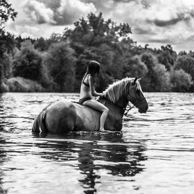 Horse rider with her faithful steed, going for a dip in the river.