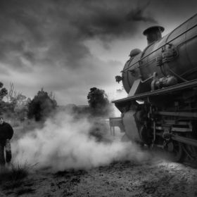 A man wanders past a steam train on its way to Pinjarra, Western Australia