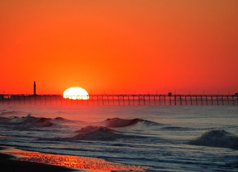 A sunrise over a pier and lighthouse in the North Caroline seashore.