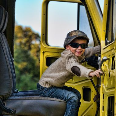Silas is giggling while he tries to close the door because he thinks he's going to drive off in the truck!