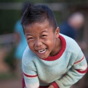 A child from the Akha tribe in Thailand laughs as I take his photo.