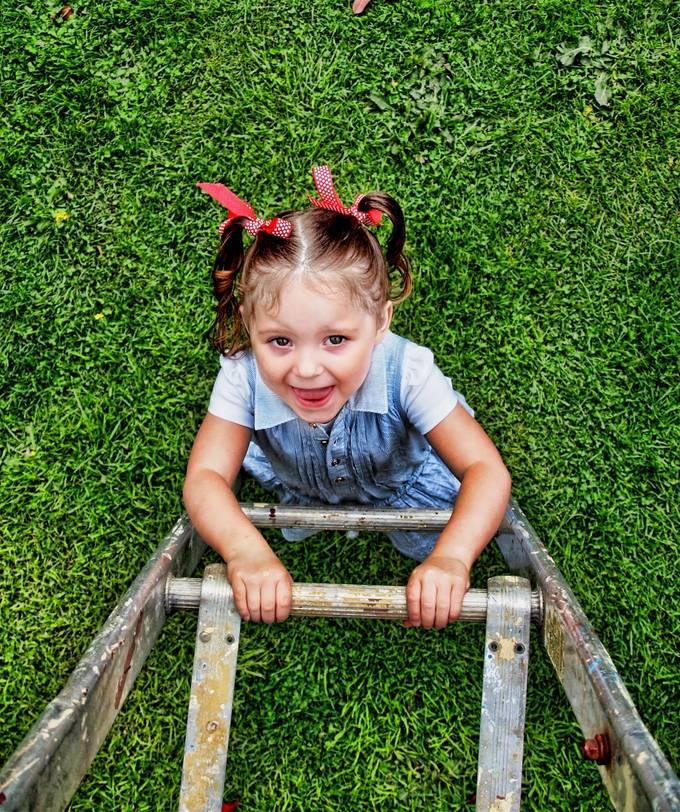 Little girl climbs a ladder.