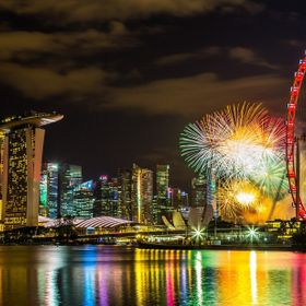 A firework display at Marina Bay Singapore showing the iconic Marina Bay Sands, Singapore Art and Science Museum, Singapore Flyer.
