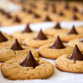 Photo of a batch of fresh baked peanut butter cookies with a chocolate drop placed in the center.