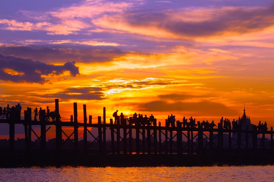 U Bein bridge-Mandalay with a beautiful procession of women carrying baskets,children with not ye...