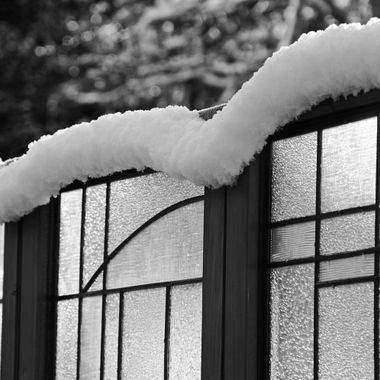 Snow sliding off the top of a privacy screen on a sunny morning.