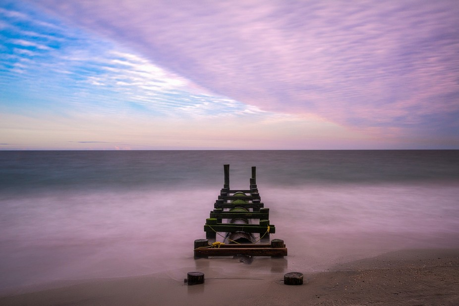 Colorful clouds roll over a pier along the Cape May, NJ shore at sunrise.