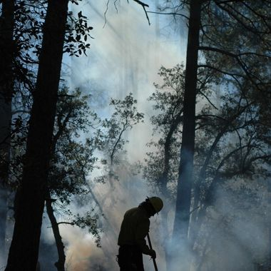 Member of AmeriCorps NCCC in Crown King, AZ assisting with burn piles.