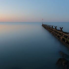 Breakwater and calm sea at sunset