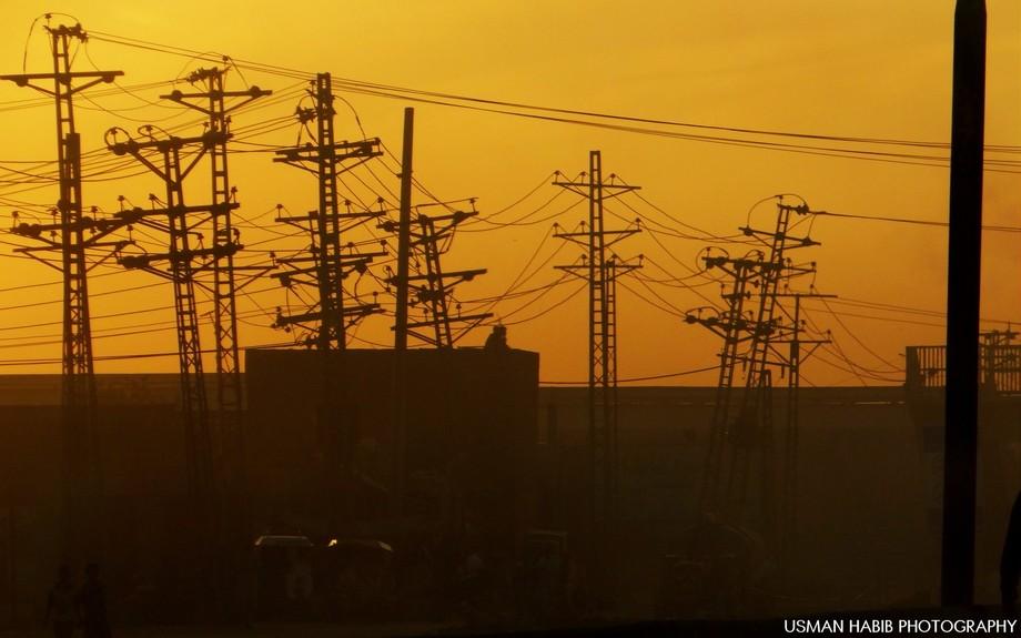 Sunset through electricity poles