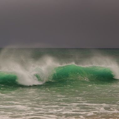 White horses as waves dance before an approaching rainstorm.