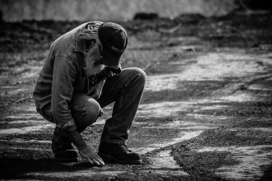 A man examining the soil where he found a piece of flint rock.