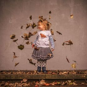 Falling leaves around a child.,
