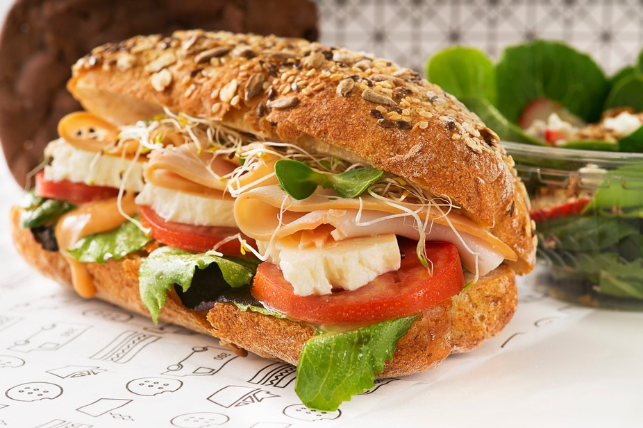 Delicious gourmet turkey sub on a multigrain hoagie, with fresh white cheese, soy sprouts, tomato...