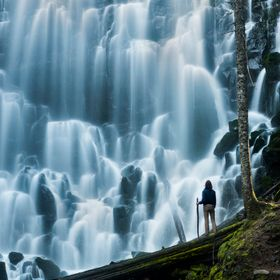 Hiker stands in awe beneath a massive falls.