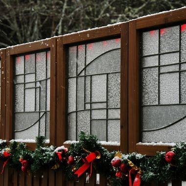 A patio privacy screen with Christmas lights and garland.