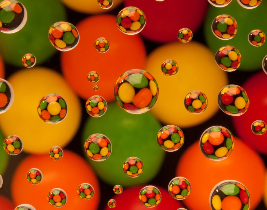 Water drops suspended above colored candies.  Yum!