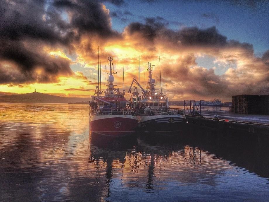 Two small Irish fishing boats,waiting to unload their catch of mackerel,in Shetland.