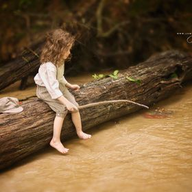 boy in vintage clothing, playing in a creek with a stick