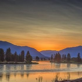 Driving on Hwy 200 coming into Plains, Montana at sunset along the Clark Fork River. This is a 3 shot stitched panorama.
