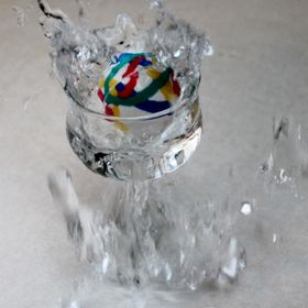 Splash,  Freeze frame of a bouncy ball dropped in a clear glass filled with water.
