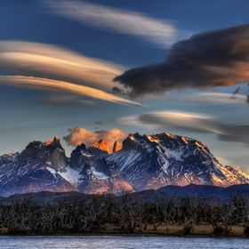 Lenticular clouds form over the horns of Torres del Paine in the National Park in Chile, South America.
