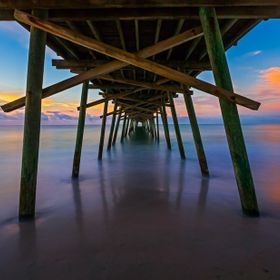 Early morning sunrise light colors the sky and sea at Emerald Isle North Carolina's Bogue Inlet Pier.