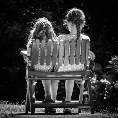 Two little girls on one chair