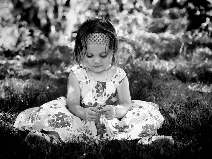 Little girl looking at a buttercup.