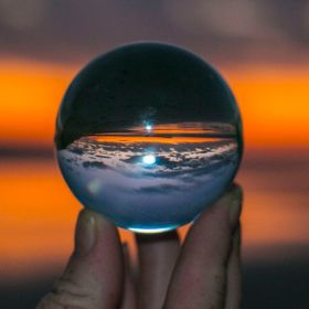 A Glass ball with the sunset and the sky reflecting on the sand in the ball.