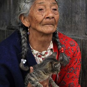 A poor elderly Hispanic woman holding a cat next to a building in Cotacachi, Ecuador