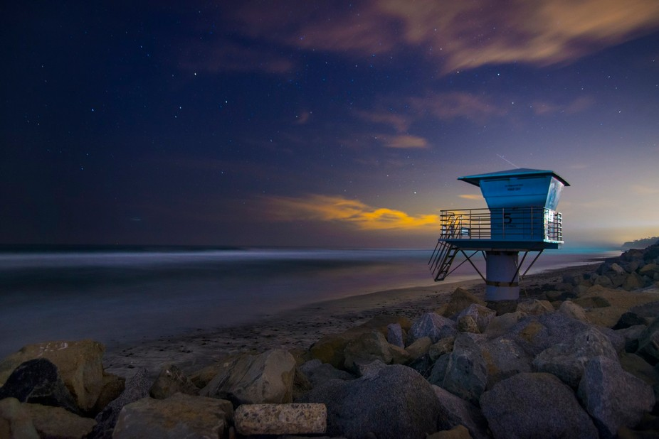 The stars shine above the water as the lifeguard tower is lit with a bluish glow