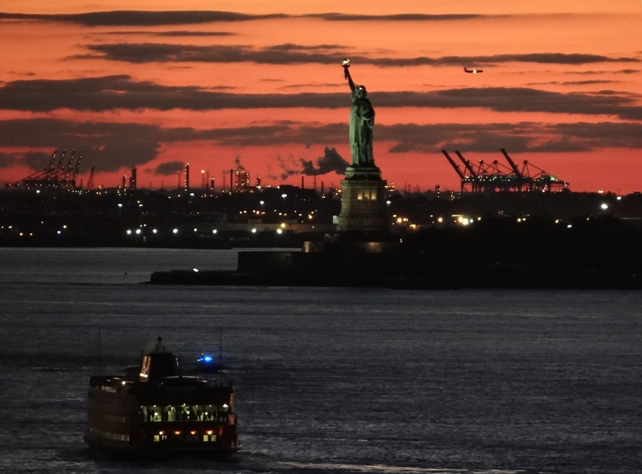 Sunset view of the industrial side of the statue of liberty and cargo cranes from Brooklyn New York