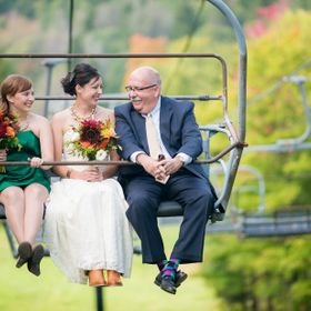 Twin Sister, Father of the Bride, and the Bride ride a chair lift to the ceremony site at the top of the mountain.