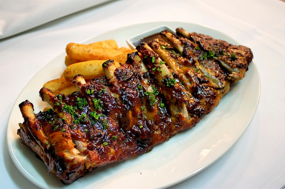 Rack of Pork ribs marinated cooked and smothered in smoked hickory sauce.