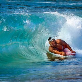 A close-up view, through the curling wave, of a young male holding on tightly to his boogie board while yelling
