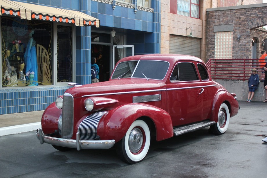 Antique or Vintage 2 door coupe. Color Red with large whitewalls. Beautiful curves.