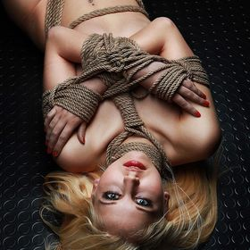 Nude blonde model, tied arms and hips lying on a black floor - Fine Art of Bondage. Fine Art photo book project about bondage/shibari (japanese b...