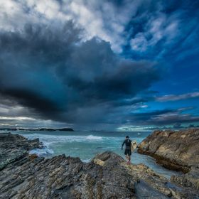 A surfer head's into the surf at Currumbin Rock on the Gold Coat Australia. At the same time a large rain cell system is forming ahead of him. Lo...